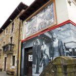 """119. …pod picassowską """"Guerniką"""" mural z ludźmi patrzącymi na bombowce."""